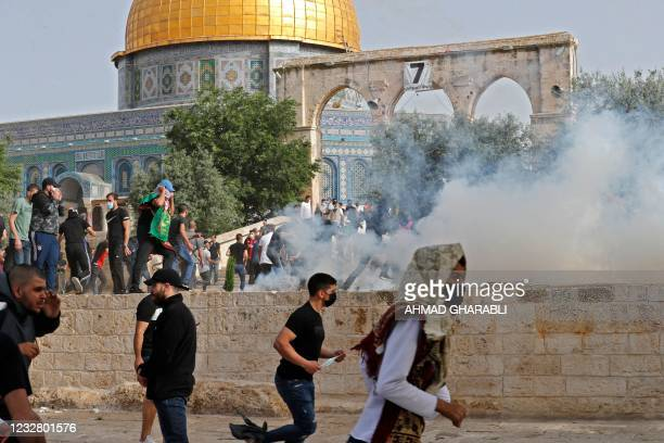 Palestinian protesters run for cover from tear gas fired by Israeli security forces amid clashes at Jerusalem's Al-Aqsa mosque compound on May 10...