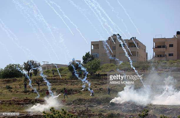 Palestinian protesters run for cover from tear gas fired by Israeli security forces during clashes next to the Israeli Ofer prison in the West Bank...