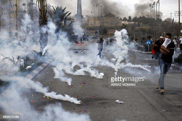 Palestinian protesters run for cover from tear gas fired by Israeli security forces during clashes in the West Bank town of AlBireh on the northern...