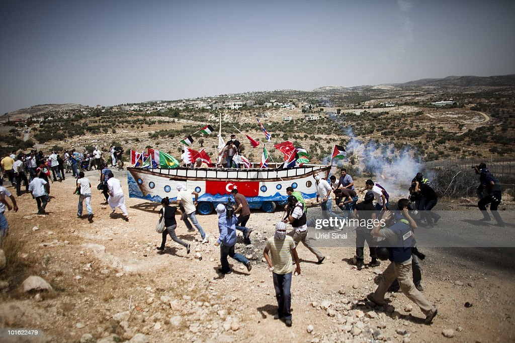 Palestinian protesters run from tear gas as they use a replica of thje Gaza aid flotilla vessel near an Israeli barrier, as they object to Israel's attack on the flotilla earlier this week, on June 4, 2010 in Bil'lan, the West Bank. Israel has faced international criticism over the deadly raid on May 31, aboard a ship carrying humanitarian aid to the Gaza Strip.