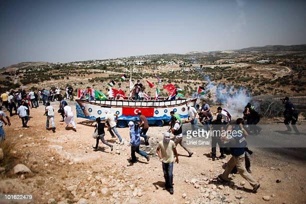 Palestinian protesters run from tear gas as they use a replica of thje Gaza aid flotilla vessel near an Israeli barrier as they object to Israel's...