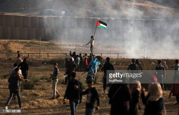 Palestinian protesters run from tear gas fired by Israeli forces amid clashes during a demonstration along the border with Israel east of Bureij in...