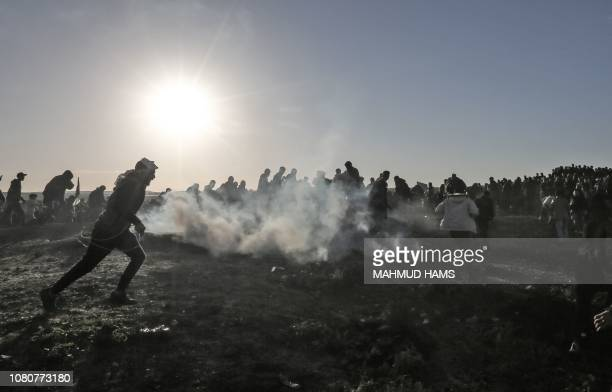 TOPSHOT Palestinian protesters run through tear gas fumes during clashes with Israeli forces following a demonstration along the border with Israel...