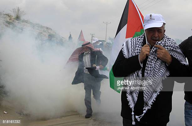 Palestinian protesters run to take cover from tear gas smoke during clashes with Israeli security forces following a demonstration to mark Land Day...