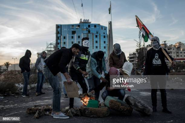 Palestinian protesters set fire to tires to create a barricade during clashes with Israeli border guards near an Israeli checkpoint on December 9...