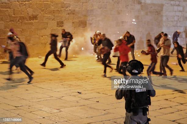 Palestinian protesters sprint away amid tear gas during clashes with Israeli security forces at the al-Aqsa mosque compound in Jerusalem, on May 7,...