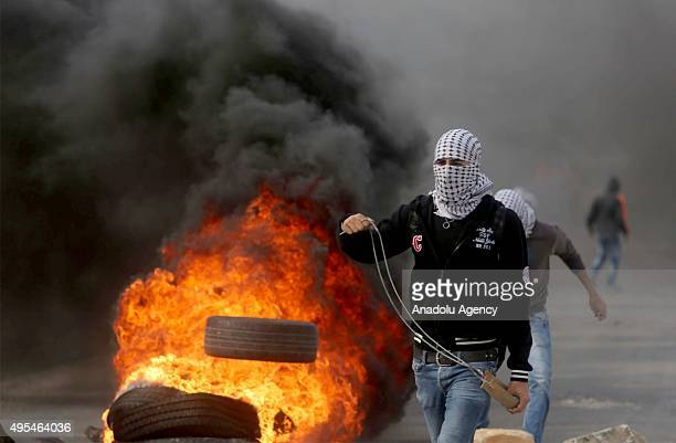 Palestinian protesters stand next to burning tyres during clashes between Israeli soldiers and Palestinians who protest Israeli violations outside...