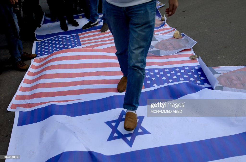 Palestinian protesters step on US and Israeli flags followiing US President Donald Trump's decision to recognise Jerusalem as the capital of Israel, in Gaza City, on December 7, 2017. /
