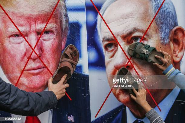TOPSHOT Palestinian protesters stick their footwear on posters depicting the faces of US President Donald Trump and Israeli Prime Minister Benjamin...