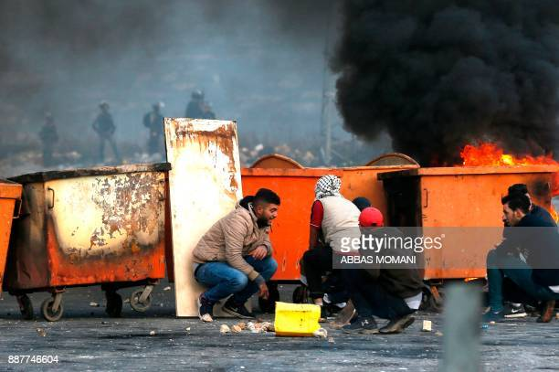 Palestinian protesters take cover behind dust bins during clashes with Israeli troops following a demonstration against US President Donald Trump's...