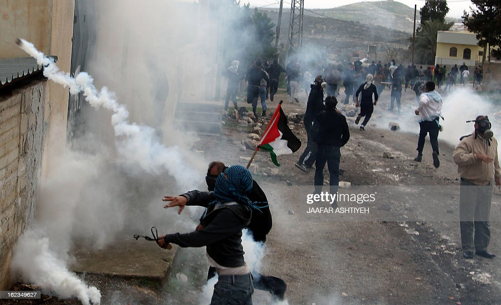 Palestinian protesters take cover from tear gas fired by Israeli troops during clashes following a demonstration in support of Palestinian hunger-striking prisoners and against the expropriation of...
