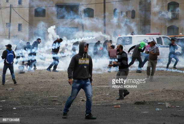 Palestinian protesters take cover from tear gas fired by Israeli security forces during clashes in Ramallah in the Israeli occupied West Bank on...