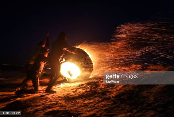 Palestinian protesters take part in a night demonstration near the fence along the border with Israel in Rafah in the southern Gaza Strip on March 19...