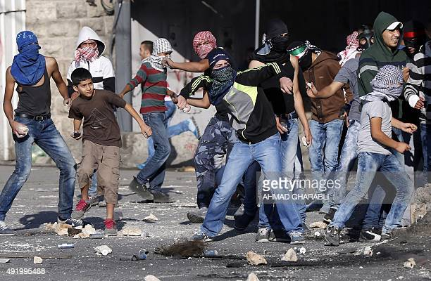 Palestinian protesters throw stones during clashes with Israeli security forces standing next to Israel's controversial separation wall in the...