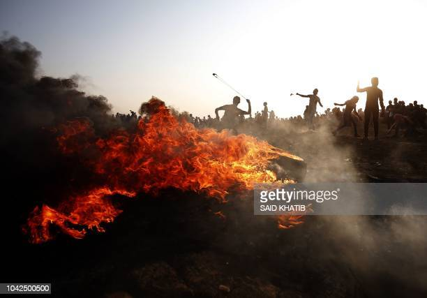 TOPSHOT Palestinian protesters throw stones toward Israeli forces during clashes along the Israeli border fence east of Gaza City on September 28 2018