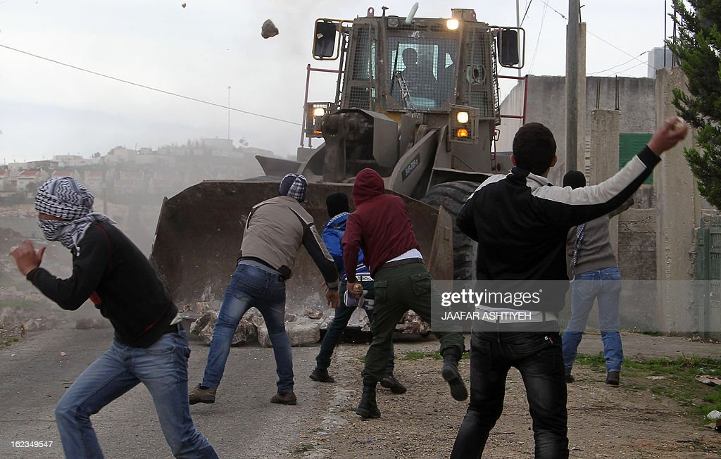 Palestinian protesters throw stones towards an Israeli military bulldozer during clashes following a demonstration in support of Palestinian hunger-striking prisoners and against the expropriation of Palestinian land by Israel in the village of Kfar Qaddum near Nablus in the occupied West Bank on February 22, 2013. Palestinians demanding the release of hunger-striking prisoners clashed with Israelis in the West Bank and east Jerusalem, as three fasting inmates were taken to hospitals.