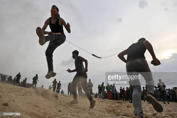 TOPSHOT Palestinian protesters throw stones towards Israeli forces during clashes on the beach near the maritime border with Israel in the northern...