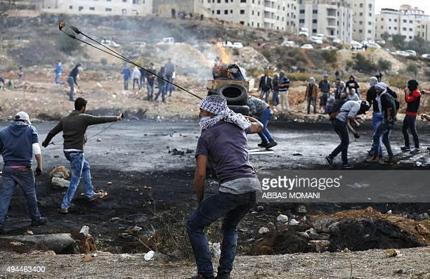 Palestinian protesters throw stones towards Israeli security forces during clashes at the northern entrance of the West Bank town of AlBireh on the...