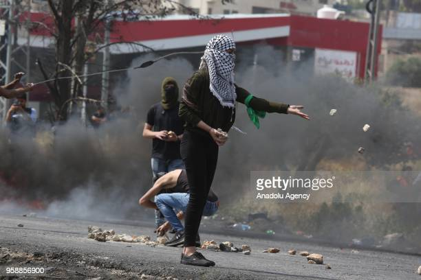 Palestinian protesters throw stones towards Israeli security forces during a protest organized to mark 70th anniversary of Nakba also known as Day of...