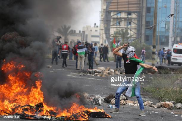 Palestinian protesters throw stones towards Israeli security forces as they burn tyres during a protest organized to mark 70th anniversary of Nakba...