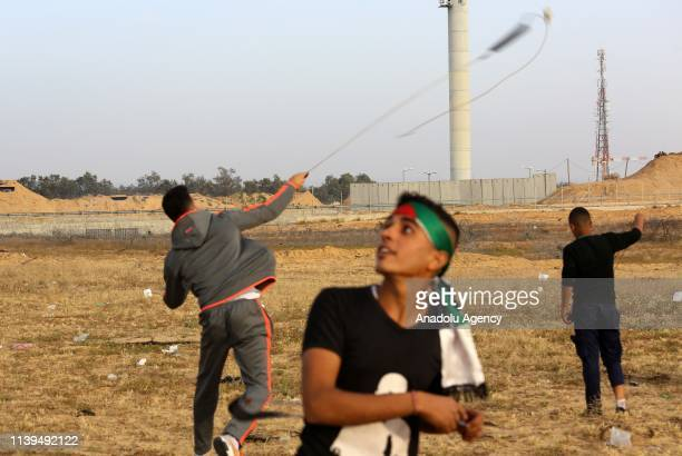 Palestinian protesters throw stones with slingshots to Israeli forces during a protest within the Great March of Return demonstration near IsraelGaza...