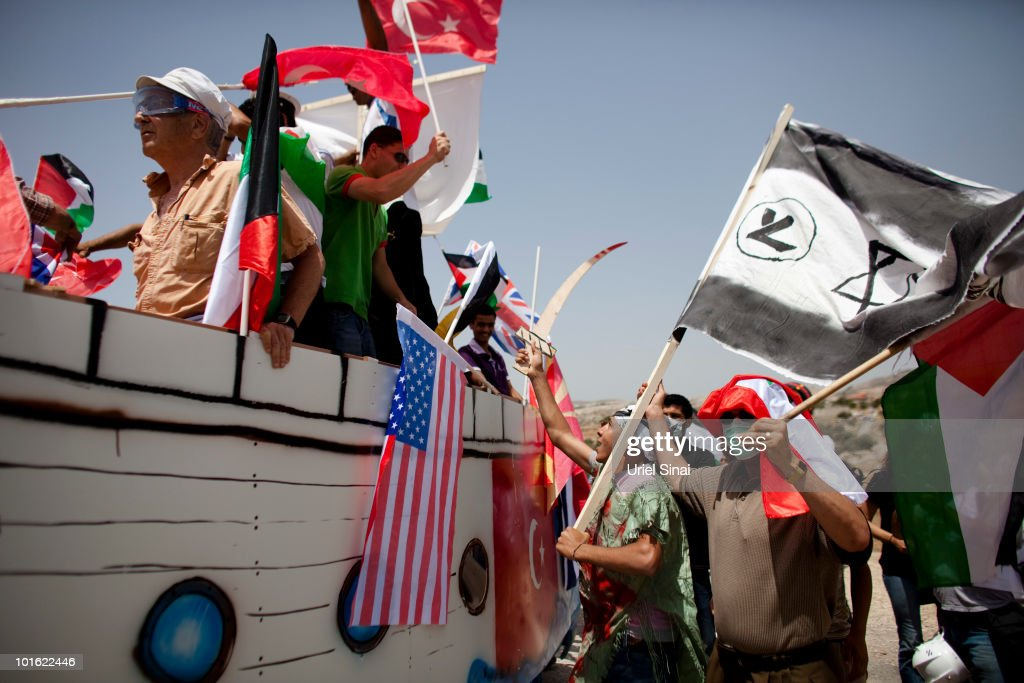 Palestinian protesters use a replica of a Gaza Aid flotilla vessel near an Israeli barrier, as they object to Israel's attack on the flotilla earlier this week, on June 4, 2010 in Bil�lan, the West Bank. Israel has faced international criticism over the deadly raid on May 31, aboard a ship carrying humanitarian aid to the Gaza Strip.