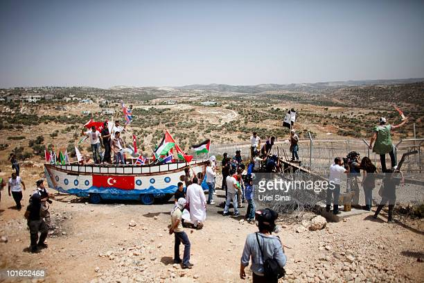 Palestinian protesters use a replica of the Gaza aid flotilla near an Israeli barrier as they object to Israel's attack on the flotilla earlier this...