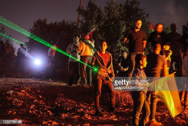 Palestinian protesters use laser torches during a demonstration against the Israeli settlers' outpost of Eviatar, in the town of Beita, near the...