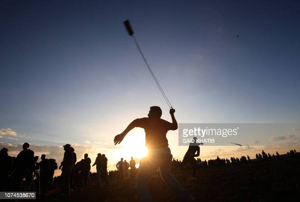 TOPSHOT Palestinian protesters use slingshots to hurl stones during a demonstration near the border between Israel and Khan Yunis in the southern...