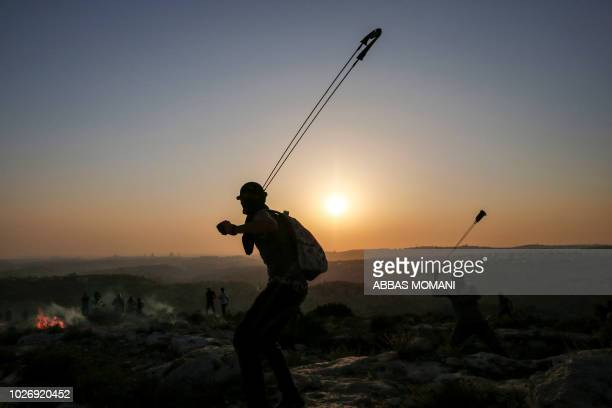 TOPSHOT Palestinian protesters use slingshots to hurl stones during clashes with Israeli security forces in the village of Ras Karkar west of...