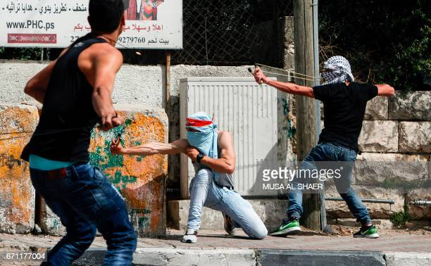 TOPSHOT Palestinian protesters use slingshots to hurl stones towards Israeli security forces during clashes following a demonstration in the West...