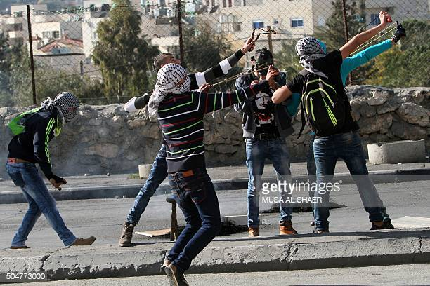 TOPSHOT Palestinian protesters use slingshots to throw stones towards Israeli security forces during clashes in the West Bank town of Bethlehem...