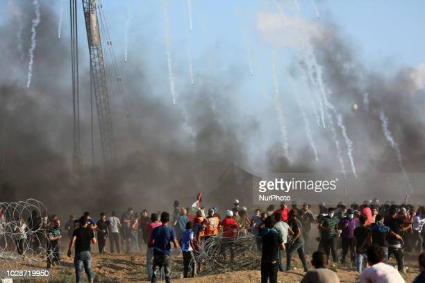 Palestinian protesters watch as tear gas grenades fired by Israeli forces fall during clashes following a demonstration along the IsraelGaza border...
