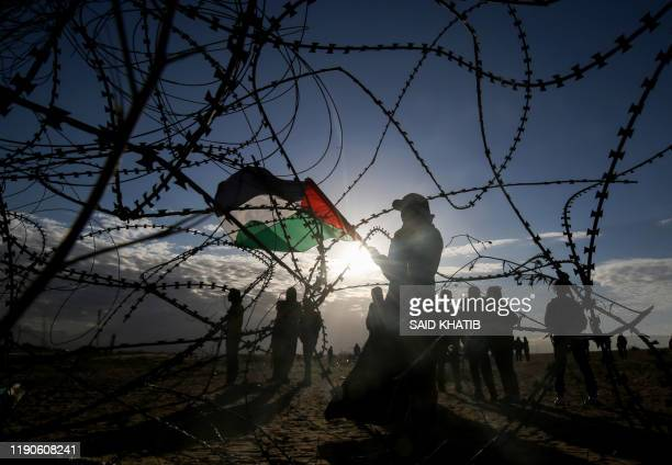 Palestinian protesters wave a national flag near concertina wire at the Israel-Gaza border, east of Rafah in the southern Gaza Strip, on December 27,...