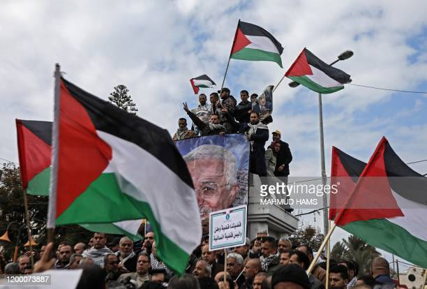 Palestinian protesters wave national flags and portraits of president Mahmud Abbas during a demonstration against a US-brokered peace proposal in...