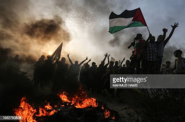 TOPSHOT Palestinian protesters wave national flags as they stand near burning tyres during a demonstration on the beach near the maritime border with...