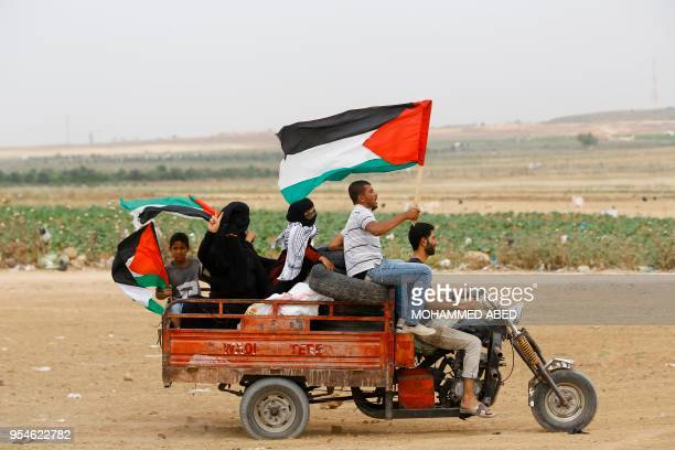 Palestinian protesters wave national flags as they transport tyres on a motorcycle car to burn them during protests near the border fence between...
