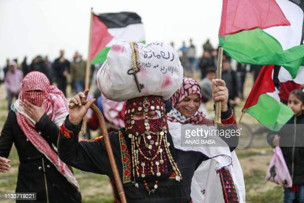 Palestinian protesters wave national flags during a demonstration marking the first anniversary of the March of Return protests near the border with...