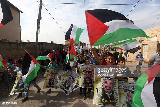 Palestinian protesters wave the national flag and carry posters of Palestinian leader Yasser Arafat during a demonstration to mark the 12th...