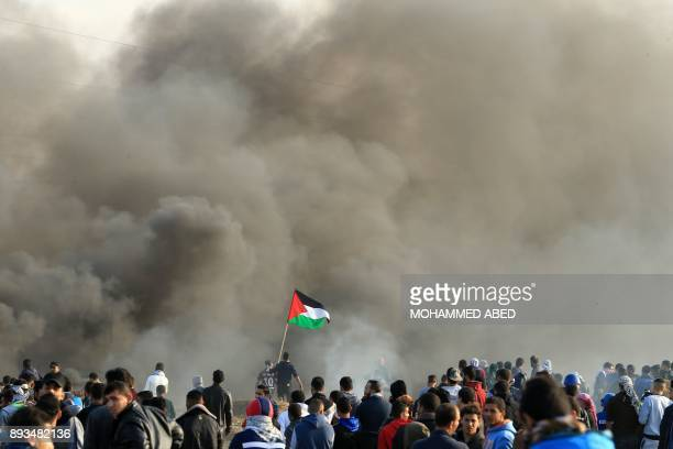 TOPSHOT Palestinian protesters wave the national flag during clashes with Israeli security forces near the border fence with Israel east of Gaza City...