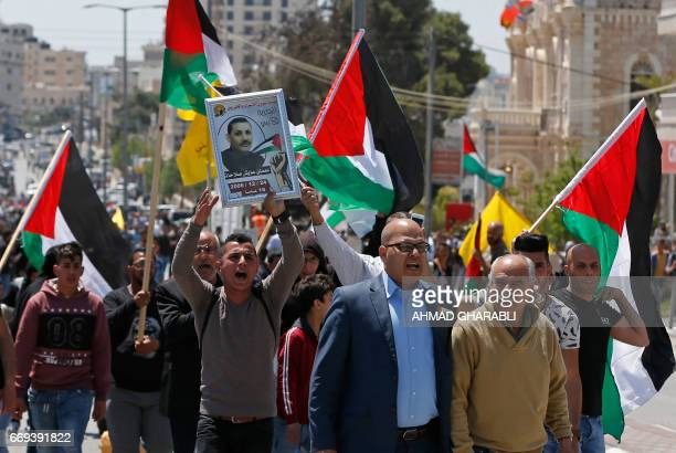Palestinian protesters wave their national flag during a demonstration in the West Bank town of Bethlehem to show their support for Palestinians...