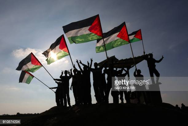 Palestinian protesters wave their national flag near the Israel-Gaza border east of the southern Gaza Strip city of Khan Yunis as they demonstrate...