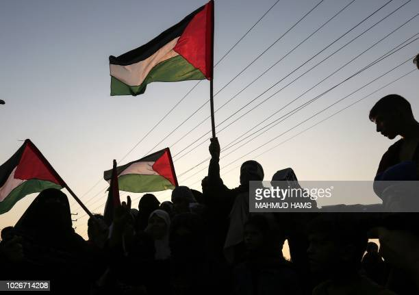 TOPSHOT Palestinian protesters wave their national flags at sunset during a demonstration near the Erez crossing with Israel on September 4 in the...