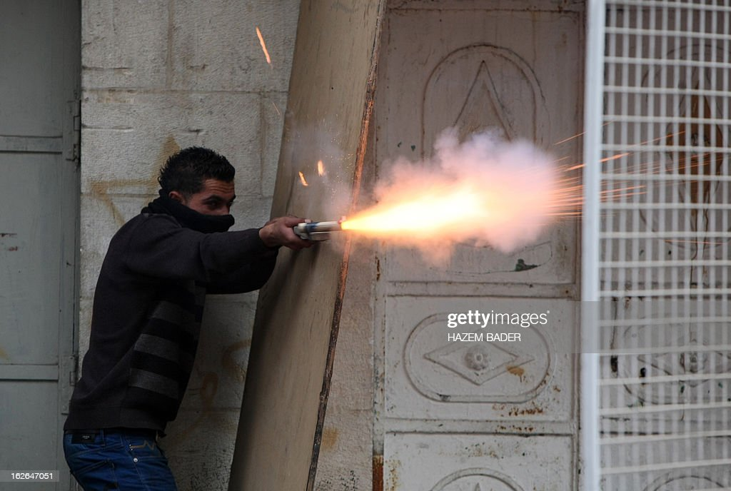 A Palestinian protestor aims sparks from a flare towards Israeli security forces during clashes near the Israeli checkpoint in the West Bank town of Hebron on February 25, 2013, following the funeral of a Palestinian man who died in an Israeli prison. Thousands of angry mourners attended the West Bank funeral of Arafat Jaradat who the Palestinians say was tortured to death in an Israeli jail, as masked militants vowed to take revenge.