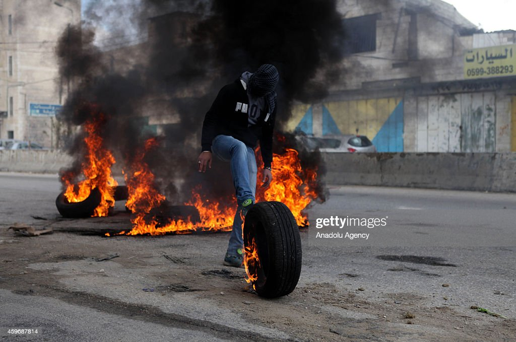 A Palestinian protestor burns a tyre during the protest against Israeli government's restrictions on Al Aqsa Mosque, on November 28, 2014, in Ramallah, West Bank.
