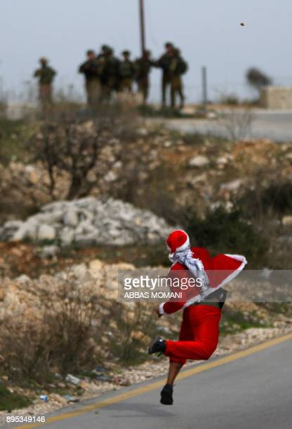 Palestinian protestor dressedup as Father Christmas throws stones towards Israeli security forces during clashes at Atarot checkpoint on the northern...