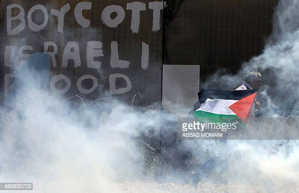 A Palestinian protestor holds his national flag as he walks near a section of Israel's separation barrier amidst tear gas smoke fired by Israeli...