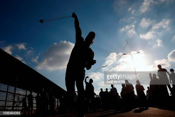 Palestinian protestor hurls a rock during a demonstration at the Erez crossing with Israel on September 18 in the northern Gaza Strip Israel has...