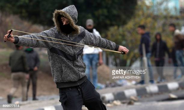 A Palestinian protestor hurls rocks towards Israeli security forces during clashes at Hawara checkpoint south of the West Bank city of Nablus during...