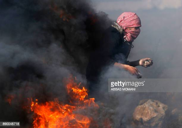 Palestinian protestor prepares to throw stones towards Israeli security forces during clashes in the West Bank city of Ramallah on December 11 2017...